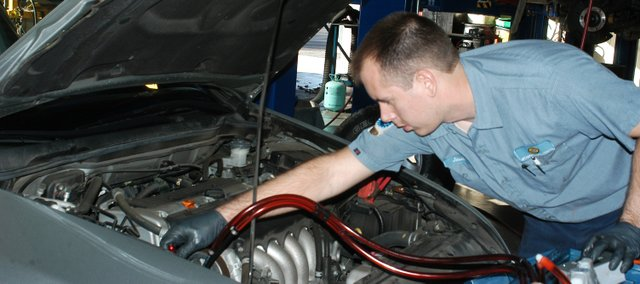 Jason Kreuger works on the power steering of a vehicle at Weaver's Auto Center in Shawnee.