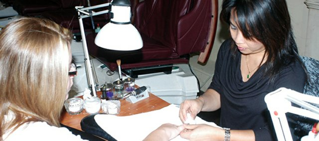 Pat Sirivongxay takes the color off of Amy Storm's nails Tuesday at NailCare studio. NailCare will contribute a dollar amount to local schools for every manicure and/or pedicure done at the studio.