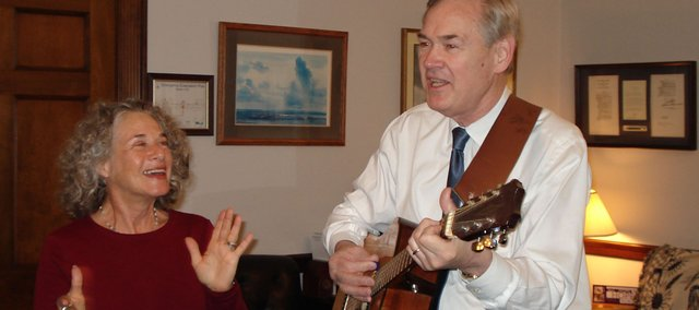 Congressman Dennis Moore, D-Kan., strums away on his guitar and sings a tune, while Carole King claps to the beat. Moore said he often plays guitar in his office to relieve some of the everyday stress of his work.