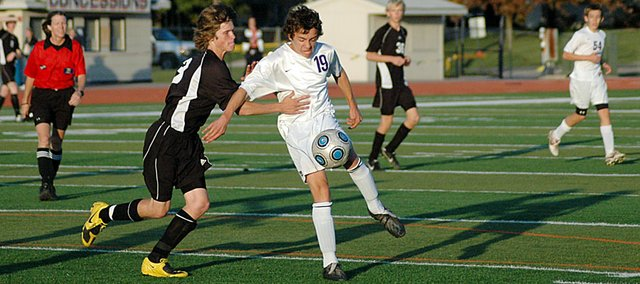 Baldwin High School sophomore Louis Joslyn, center, fights off a Paola defender to gain possession of the ball Monday afternoon. Joslyn scored Baldwin's first goal, but the Bulldogs lost 3-2 in overtime.
