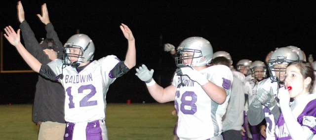 Baldwin High School freshman Tyler Cawley (No. 12) and junior Tyler Schneider celebrate a Bulldogs' touchdown Friday night. Baldwin defeated Santa Fe Trail 62-10 to win its first game of the season.