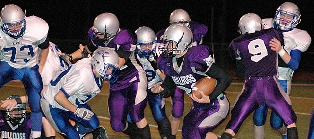 Baldwin High School junior Ryan Rogers, center, follows his blockers during a run in the second quarter Friday. Rogers scored one touchdown as BHS defeated Perry-Lecompton 36-21 to qualify for the Class 4A playoffs.