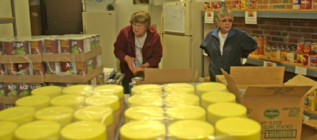 Jan Vaughn and Rosie Inman sort through food for shelving Monday at the De Soto Multi-Service Center. The abundance of food at the community food pantry was unusual and stemmed for the monthly delivery of USDA commodities to the center for those qualifying  for the food. Vaughn and Inman are two of eight De Soto United Methodist Women who volunteer to manage the food pantry two days a week.