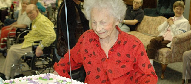 Medicalodges, Eudora resident Henrietta Olson looks Thursday at a cake celebrating her 105th birthday.