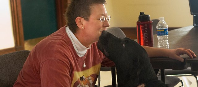 Holly Jacobs has her face licked by 3-year-old Lexi, a black Labrador with aggression problems. Jacobs, who claims to be able to communicate telepathically with animals, was in Leavenworth Saturday to discuss her ability and to provide on-on-one sessions with pet owners.