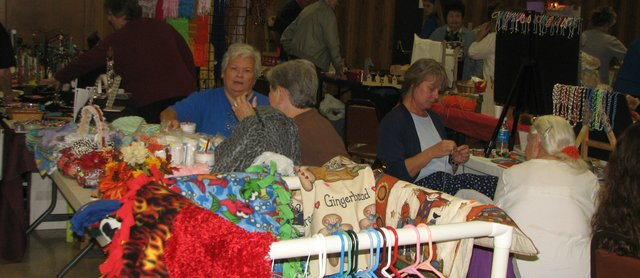 Ladies at the Holy Angels Catholic Church display their creations Saturday for customers at the annual craft fair.