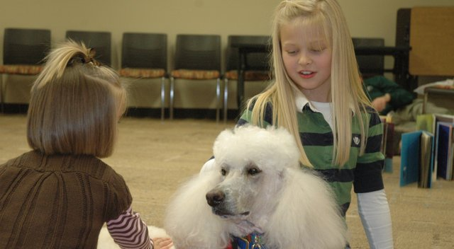 Cooper Wilcox, at left, and older sister Morgan Wilcox pet Zoe, a dog with the Reading Education Assistance Dogs program. Zoe and another R.E.A.D. dog, Llew, visited the Bonner Springs City Library Thursday night.