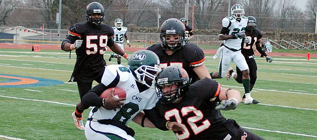 Baker University junior Matt Brock (No. 32), junior Andrew Patch and senior Alphaeus Williams (No. 59) swarm in on Central Methodist's quarterback late in Saturday's game. Baker won 33-7 on senior day.