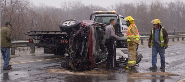 Local firefighters and a Leavenworth County Sheriff's officer work an accident scene Monday morning just west of Stranger Creek on U.S. Highway 24-40 in the eastbound lanes. Extrication was needed at the accident scene.