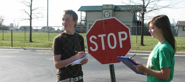 Student Council sophomores Marcas Box (left) and Jamie Crouss count how many students are wearing their seat belts when entering the Basehor-Linwood High School parking lot.