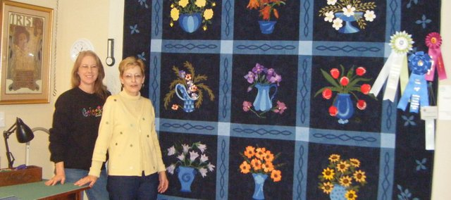 "Theresa Ward (left) and Doris Morelock Hendrickson stand next to their blue-ribbon winning quilt. Hendrickson affectionately named the quilt ""Flora Elena,"" which took her two years to complete."