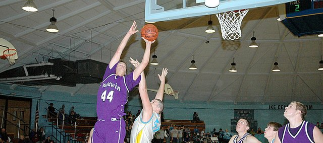 Baldwin High School junior Justin Vander Tuig (No. 44) shoots a layup over his Central Heights defender Friday night. Vander Tuig scored 19 points to lead the Bulldogs to a 53-42 victory in the season opener.