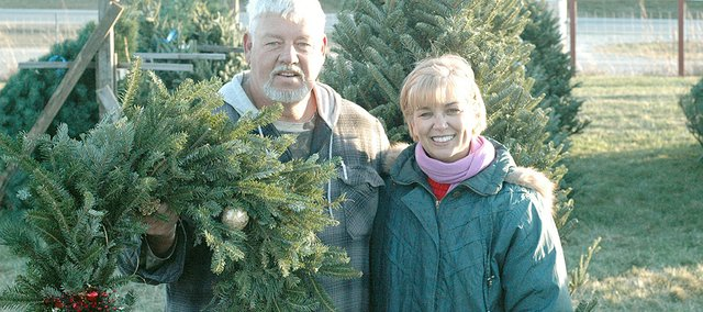 Dave and Rose House stand with a wreath in the middle of their Christmas tree lot, 1727 Oak St., just north of Kansas Highway 10. The lot is open from 4 to 8 p.m. Monday through Friday, and from 10 a.m. to 8 p.m. Saturday and Sunday.