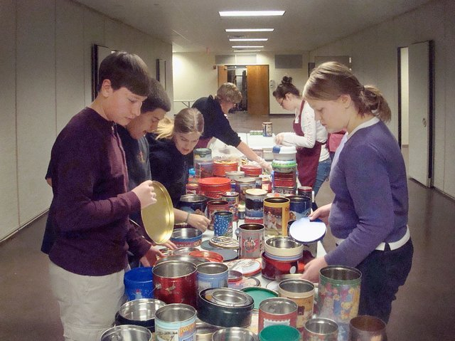 Leavenworth County 4-H Junior Leader members look through tins for holding cookies they baked with the help of parents Thursday in Tonganoxie. The group gives the cookies to Good Shepherd Thrift Store and Food Bank, which distributes them to needy families each holiday season.