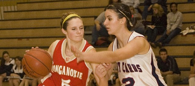 Tonganoxie's Andie Jeannin tries to drive past Eudora's Jennifer Bowser in the seventh-place game at the Paola Invitational on Friday afternoon. The Cardinals edged the Chieftains, 40-39.