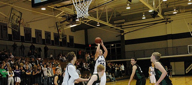 Baldwin High School senior Zach Wright attempts a jump shot over several De Soto defenders Tuesday night. Wright scored nine points in the Bulldogs' 51-41 loss.