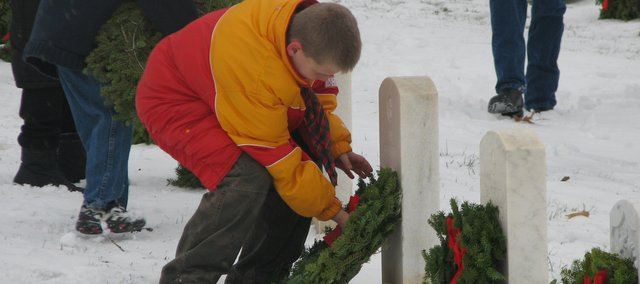 A young boy gently places a holiday wreath on the grave of a fallen veteran in Leavenworth National Cemetery. Community members gathered at the cemetery Saturday for a Wreaths Across America ceremony, a national event honoring deceased soldiers.
