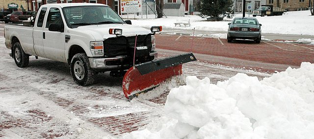 Baldwin City Public Works Director Bill Winegar continued the snow removal process Tuesday on High Street, adding to the huge mound at the corner of Seventh Street.