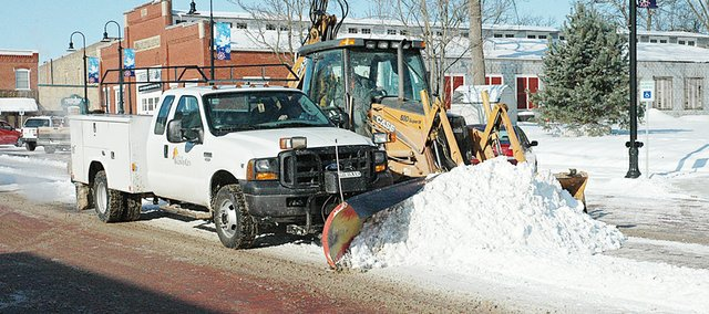 City crews used a different way to clear the middle ridge of snow down High Street Monday morning. They doubled up with the tractor and pickup to move the snow to a truck where it could be loaded and taken away. The inch to 2 inches of snow overnight Saturday had the crews busy once again.