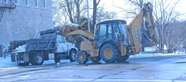 Crews work to remove mounds of snow at the intersection of Peoria and 83rd streets that were piled there during the Christmas blizzard. De Soto City Street Supervisor Ron Creason talks about that effort and other topics related to snow removal.