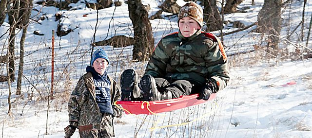 Ben Morgenstern, 12, flies through the air while Garrett Burkhart, left, also 12, looks on during a sledding excursion New Year's Eve at Signal Oak. There was a group of sledders who did all sorts of aerobatics during the day.