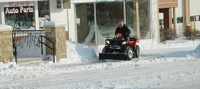 Ken Robbs had the ATV with the blade on front to clear the snow away from his business in downtown Baldwin City Thursday morning. There was scattered shoveling going on, too, but there weren't too many people out and about in the brutally conditions early in the day.
