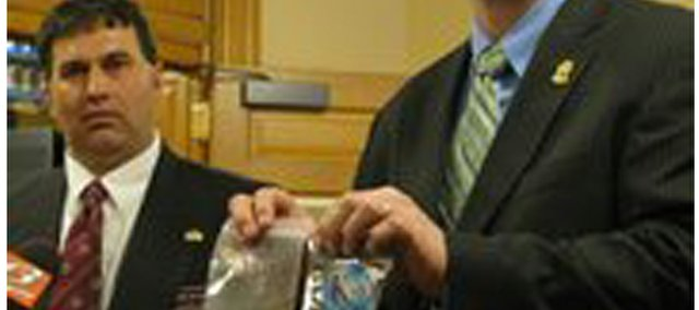 State Rep. Rob Olson (left) and Johnson County forensic scientist Jeremy Morris on Monday display K2 product that they want banned because it contains synthetic substances that they said produces intense high and could be dangerous. Olson, R-Olathe, and Johnson County law officers held a news conference at the Statehouse on the first day of the 2010 legislative session.