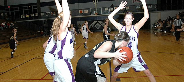 Baldwin High School juniors Allison Howard, left, and Ramie Burkhart apply full-court pressure to a Paola player during the first half Friday night. The Bulldogs beat the Panthers 54-41.