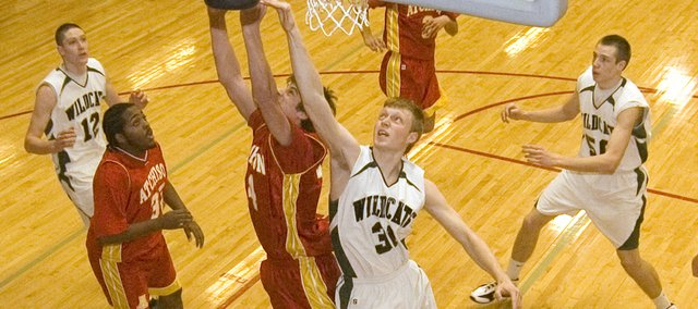 De Soto High senior Paul Stallbaumer battles Atchison in the paint for a rebound during the Wildcats' 57-45, opening-round win on Monday night at the Tonganoxie Invitational.
