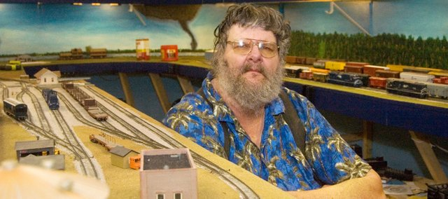 Tom Stolte sits near miniature versions of select buildings in Atchison in his model train display building.
