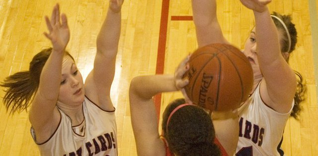 Eudora High defenders Shea Lounsbury and Victoria Lehmann trap Atchison's Alana Downing in the backcourt on Thursday at the Tonganoxie Invitational. Eudora's defense keyed a 58-33 win.