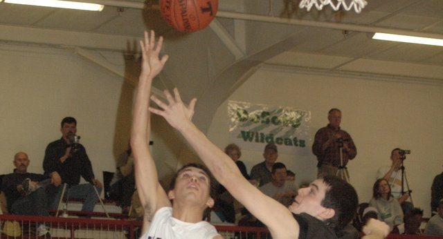 Eudora High's Conner Scott (5) drives in for a layup as De Soto's Kyle McCulloch (23) defends during the second quarter Saturday at Tonganoxie. Eudora won the third-place game 35-31.