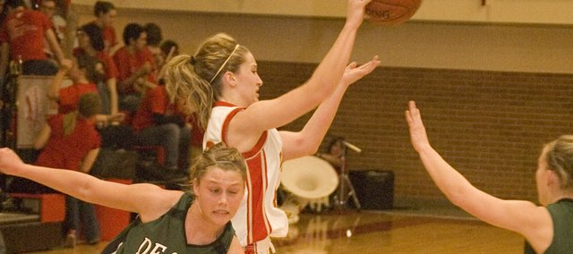 Tonganoxie High freshman guard Hannah Kemp keeps the ball away from De Soto defender Tami Crow in the Chieftains' 60-44 victory on Tuesday at THS.