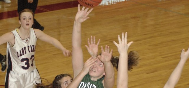 De Soto senior Katie Williams (43) drives for a shot over Eudoras Sydney Schmille and Victoria Lehmann Saturday at the Tonganoxie Invitational. The Wildcats beat the Cardinals 44-37 and finished the tournament in fifth-place.  