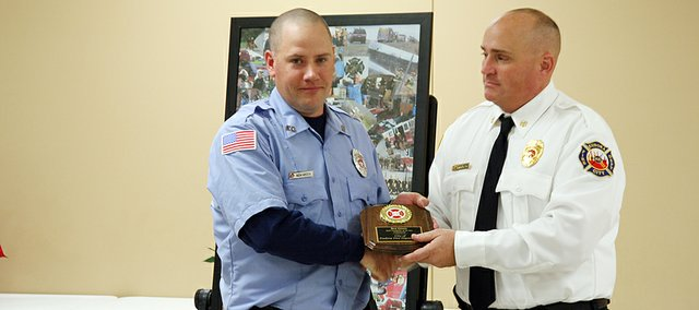 Ben Green receives the firefighter of the year award from Eudora Fire Department Deputy Chief and City Councilman Tim Reazin.