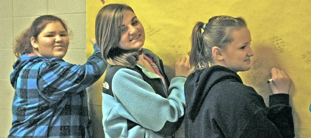 Lexington Trails Middle School seventh-graders Ciaann Chance, Kenna Hall and Bethany Drake sign a bulletin board in the school's hallway to thank their Panther Pals. The school's Student Council Forging Friendship Committee began the anonymous program to encourage new friendships.