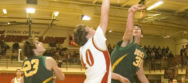 Tonganoxie High senior forward Justin Jacobs attempts to score between Basehor-Linwood defenders Ryan O'Donnell and Ryan Murphy on Tuesday night. The Bobcats prevailed, 61-52, at THS.