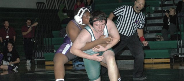 Shane Schramm wrestles against Piper's Caleb King in the heavyweight match Thursday at De Soto. Schramm's win pushed the Wildcats past the Pirates 33-30.