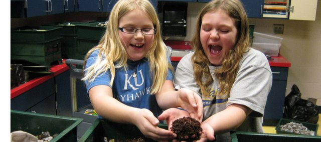 Starside Elementary students Lexi Meneely and Taylor Escobar explore the school's new composting worms. Starside received a $4,500 Green School Grant, which was used to purchase recycle bins, bio-degradable lunch trays and composting worms.