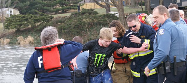 "Shawnee Fire Department personnel help Joe Clopton out of Walden Pond after an ice rescue on Dec. 21. The story of Clopton's rescue — and the lessons he used from the television show ""Man vs. Wild"" will be aired in a Discovery Channel special on Memorial Day."