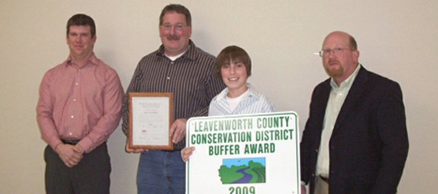 Damon New, left, and Jeff Heim, right, present the Leavenworth County Conservation District Buffer Award and Water Quality Certificate to Ken Buchholz and his son, Hunter.