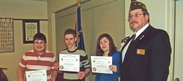 Tonganoxie Middle School students, as well as Tonganoxie High school students, recently were recognized for their winning VFW essays. Pictured from left, are TMS winners Justyn Lee Leslie, Andrew Behm and Lauren Harrell. Pictured with them is VFW Post 9271 Commander Dan Hopkins.