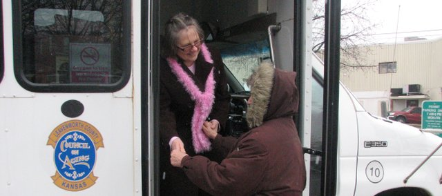 Linda Karpierz, Leavenworth County Council on Aging Senior Express supervisor, helps Patty Henchek onto the Senior Express bus. Senior Express recently expanded its services to Basehor and Tonganoxie.