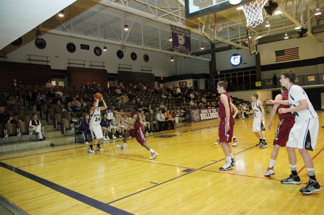 Baldwin High School senior Camdon Schwartz, left, sets his feet before shooting a three-pointer Tuesday night. Baldwin was beaten by Saint James at home, 70-40.
