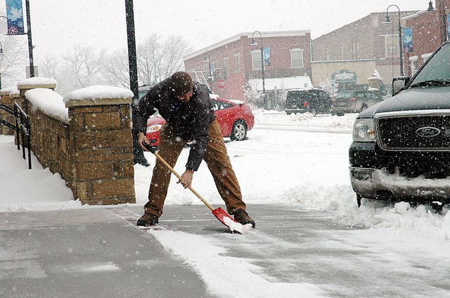 Brian Sheldon was busy Friday afternoon with an all-too-familiar chore this winter in Baldwin City as he was shoveling yet another round of snow in front of Stephens Real Estate downtown.