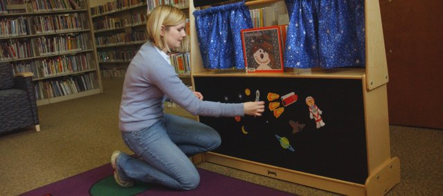 Johnson County Library youth specialist Robyn Myers places stickers on a puppet theater that is part of the 6 by 6 programs she brought Friday to De Soto. The program is designed to help parents and caregivers teach six pre-reading skills and habits to children.