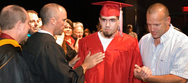 Brandon Parker, Tonganoxie High School athletics director, congratulates Austin Stone for getting his diploma. Stone, who is now blind after complications arose from medical gas he received while having his wisdom teeth removed in March, was helped through the stage at Tonganoxie High School by his dad Lance Stone.