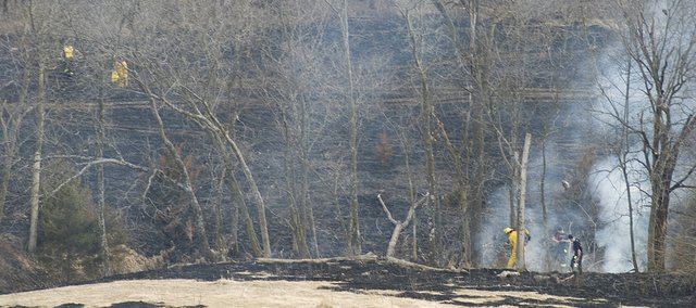Area firefighters work to put out a grass fire that started Wednesday afternoon. Emergency officials estimated that more than 100 acres of land, on 234th Street and Honeycreek Road, were burned in the fire.