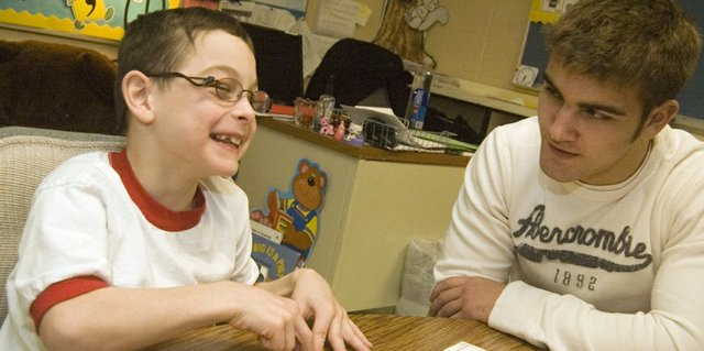 "Shane Lewis grins while working on a reading exercise with Jonas Myers in the Tonganoxie Elementary School resource room. Lewis, a second-grader at TES, works with Myers, a THS sophomore taking a ""Leadership in Sports"" class, once a week."