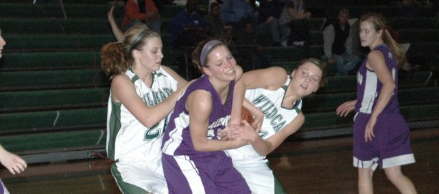 Tami Crow battles for a loose ball against Baldwin Tuesday in De Soto. The Wildcats lost the game 57-42 and fell Friday at Gardner 47-25.